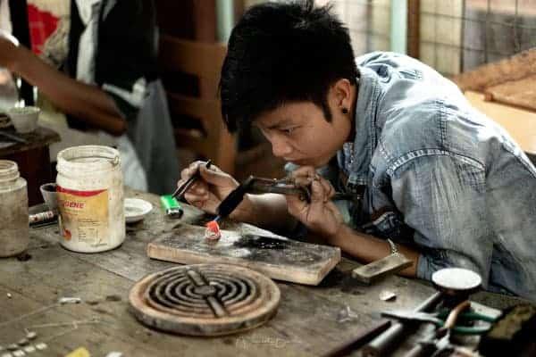 fabrique de bijoux en argent garçon au lac Inle en Birmanie
